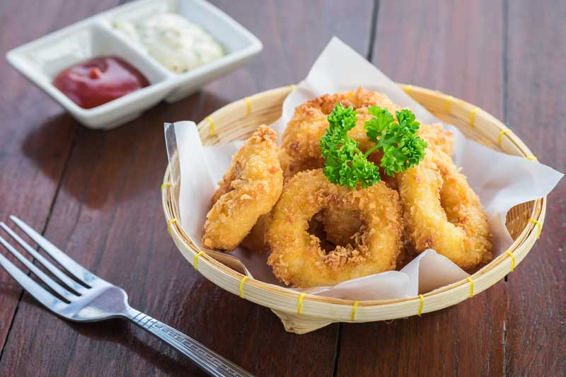 Fried calamari rings in wicker basket and sauce