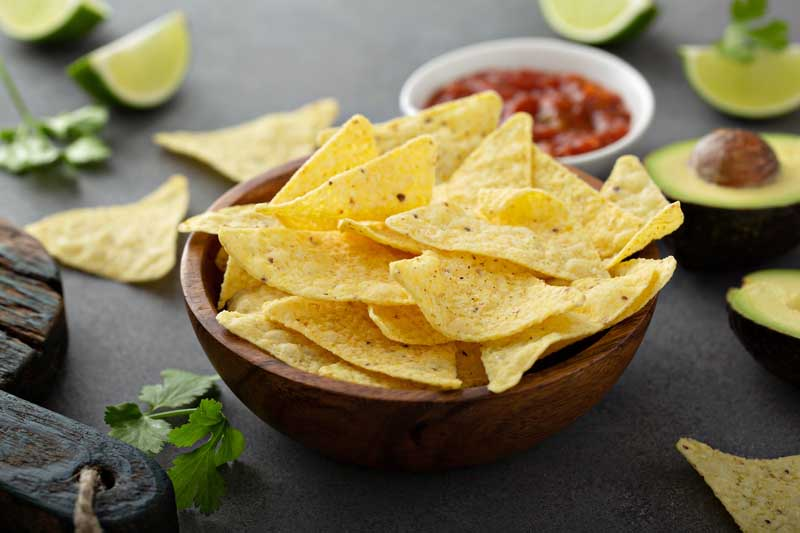 Tortilla chips in a bowl with salsa, limes and avocados