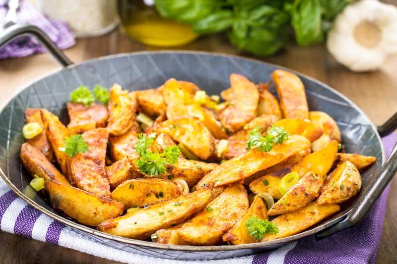 Knusprig gebratene Kartoffelspalten mit Petersilie und Frühlingszwiebeln