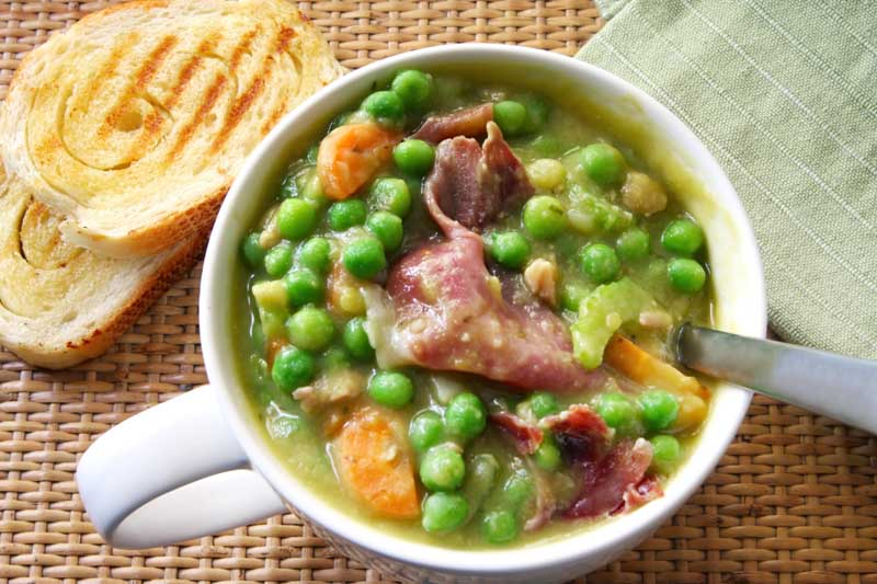 A cup of hearty pea and ham soup with crusty sourdough bread.  The ham is crispy prosciutto.